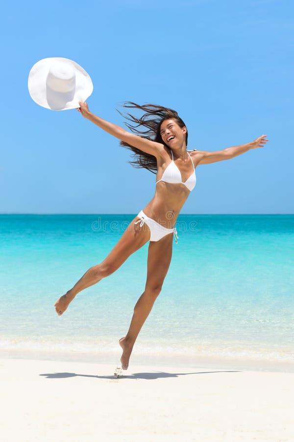 Lycklig bekymmerslös flickabanhoppning på rolig strandsemester royaltyfri foto