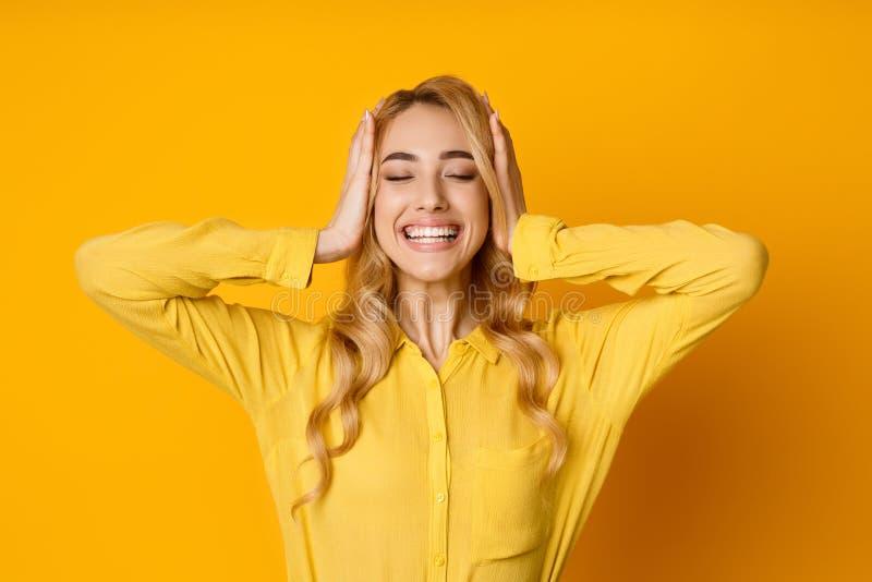 Lycklig bekymmerslös kvinna som ler och poserar med stängda ögon royaltyfri bild