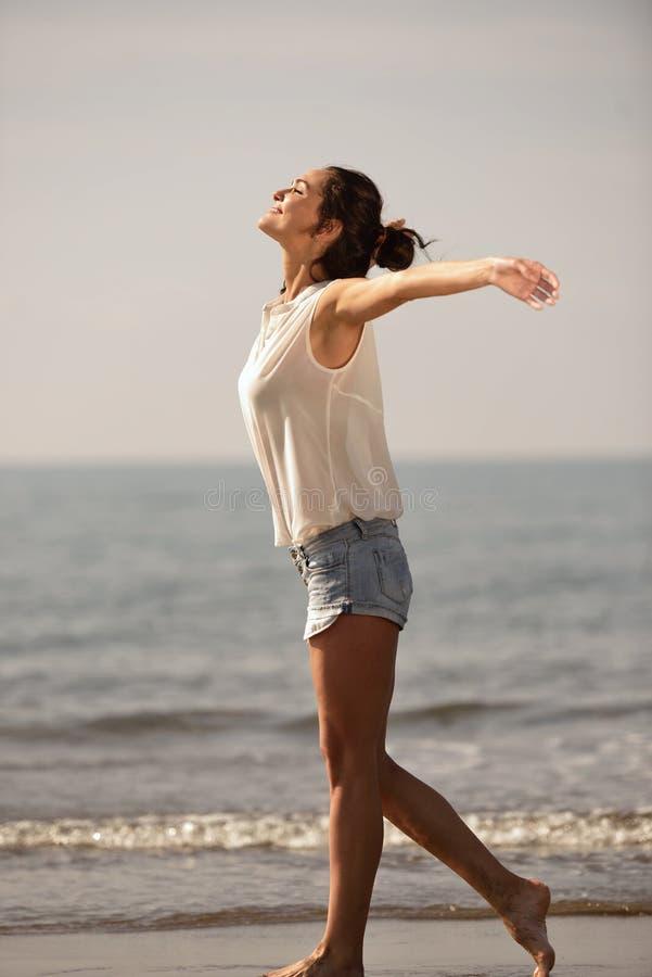 Lycklig bekymmerslös kvinna som tycker om härlig solnedgång på stranden royaltyfri foto
