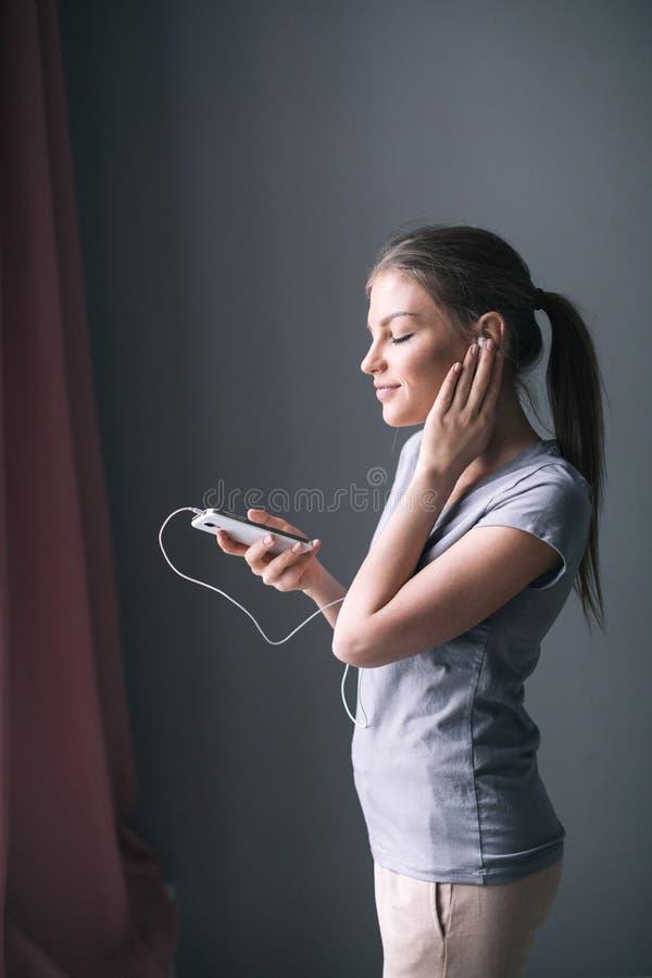 Lycklig bekymmerslös ung kvinna som lyssnar till musik från smartphonen över grå bakgrund arkivfoto