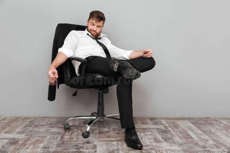 Lycklig berusad affärsman som i regeringsställning sitter stol med flaskan royaltyfri bild