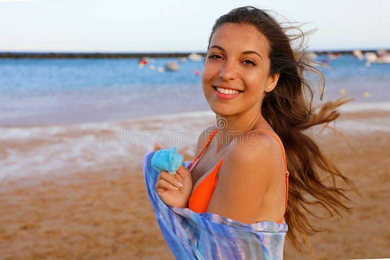 Lycklig bikinikvinna på stranden Stående av den härliga flickan med vind som fladdrar hår och pareo Sommarstående på stranden på royaltyfria bilder