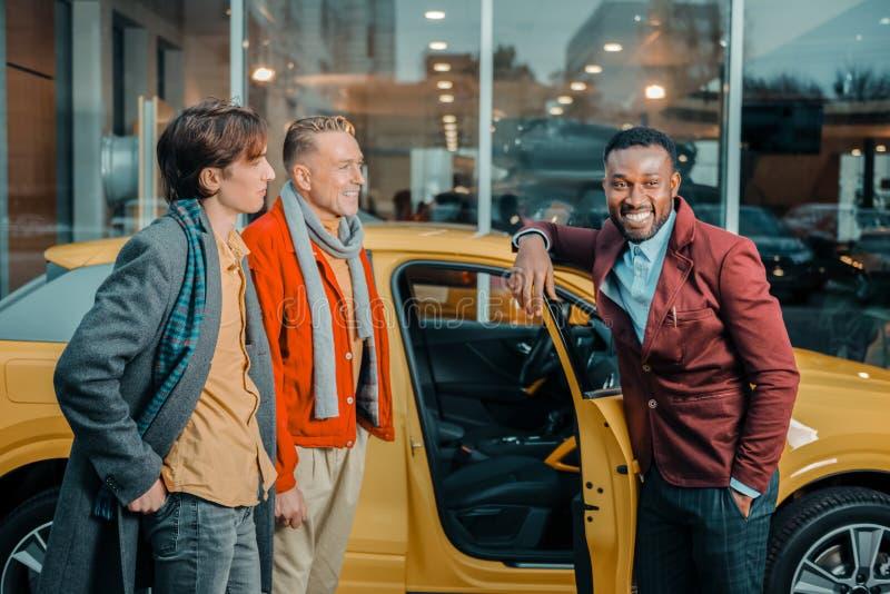 Lycklig bilåterförsäljare som säljer bilen till en familj royaltyfria bilder
