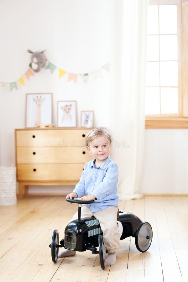 Lycklig bil f?r tappning f?r barnridningleksak Rolig unge som hemma spelar Sommarsemester och loppbegrepp Aktiv pys som k?r en bi royaltyfria foton
