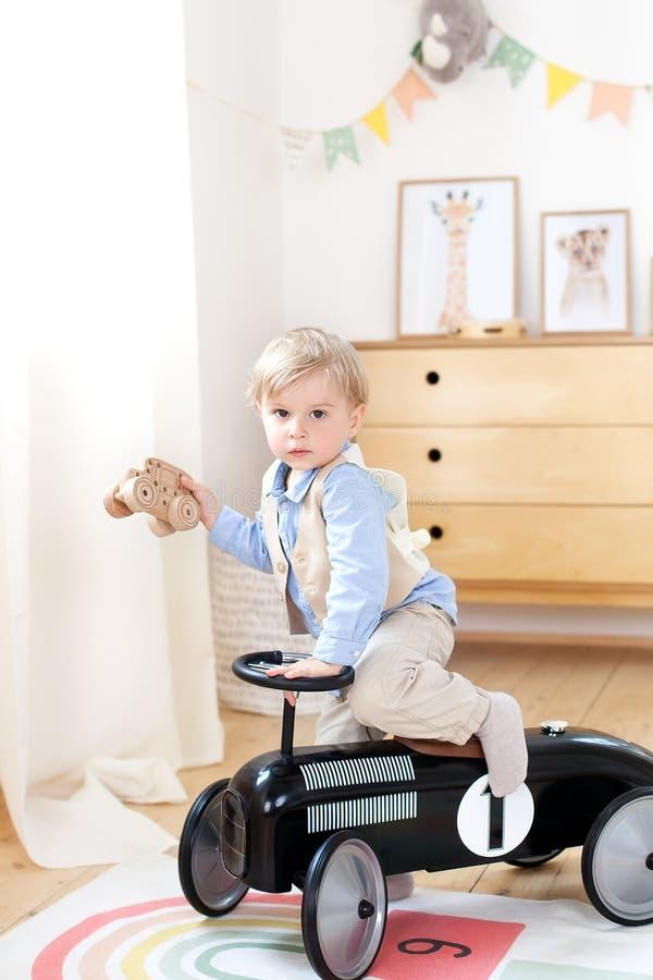Lycklig bil f?r tappning f?r barnridningleksak Rolig unge som hemma spelar Sommarsemester och loppbegrepp Aktiv pys som k?r en bi arkivfoton