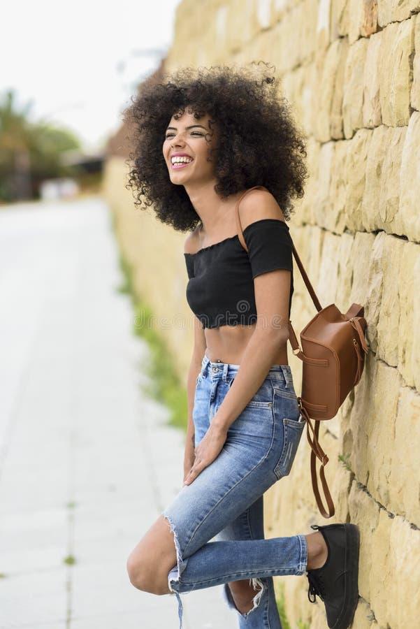 Lycklig blandad kvinna med afro hår som utomhus skrattar fotografering för bildbyråer
