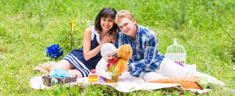 Lycklig blandad Racefamilj som har en picknick och leker i parkera royaltyfria bilder