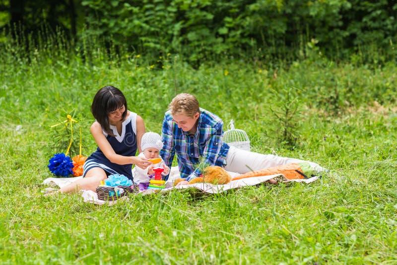 Lycklig blandad Racefamilj som har en picknick och leker i parkera royaltyfri fotografi