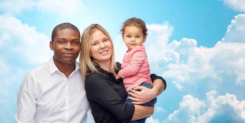 Lycklig blandras- familj med det lilla barnet arkivfoton