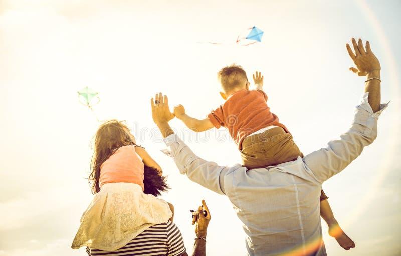 Lycklig blandras- familjgrupp med föräldrar och barn som spelar med draken på strandsemestern - sommarglädjebegrepp royaltyfri bild