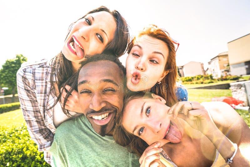 Lycklig blandras- vängrupp som tar selfie som ut klibbar tungan med roliga framsidor - ungdomarsom delar berättelser på socialt fotografering för bildbyråer