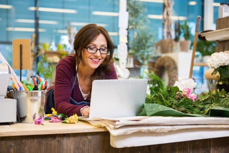 Lycklig blomsterhandlareUsing Laptop At räknare i blomma arkivbilder