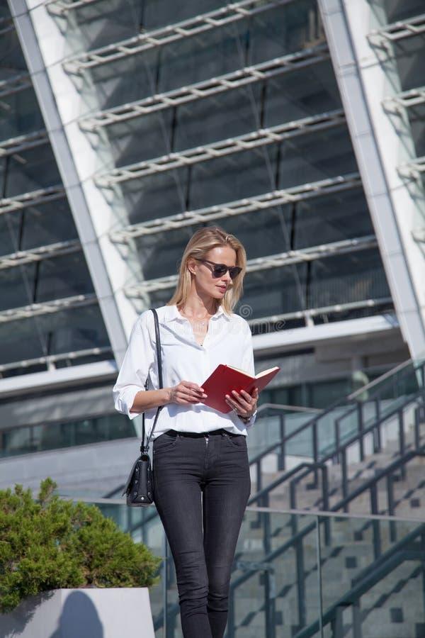 Lycklig blond affärskvinna i solglasögon med anteckningsboken mot av modern byggnad royaltyfria bilder