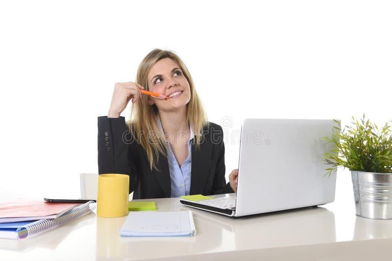 Lycklig blond affärskvinna som arbetar på datoren på att tänka för kontorsskrivbord royaltyfria bilder