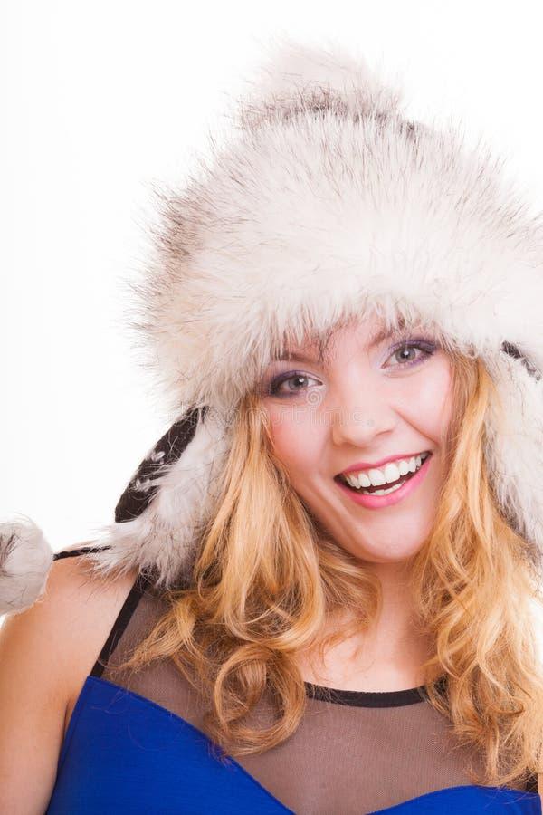 Lycklig blond flicka i varm pälshatt. Vinterkläder. Mode och skönhet. royaltyfri bild
