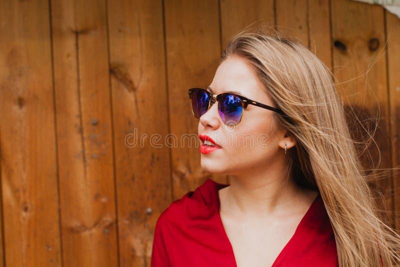 Lycklig blond flicka med röd kläder och kanter royaltyfri fotografi