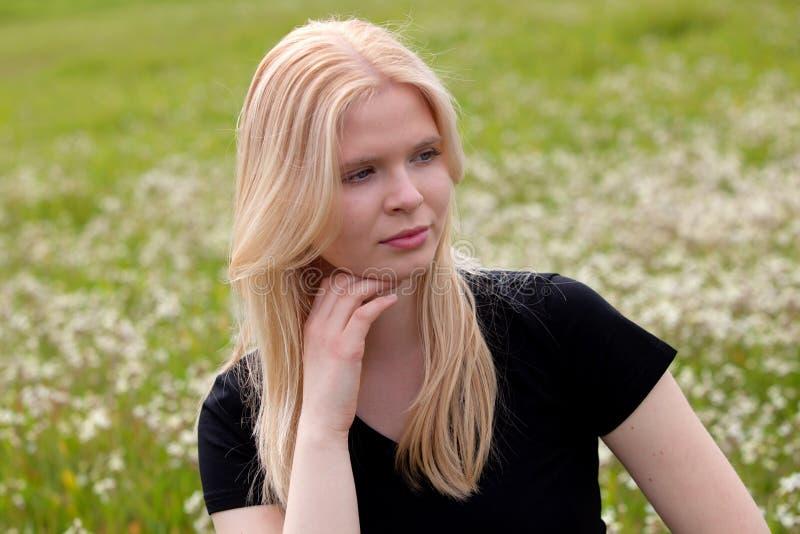 Lycklig blond flicka som omges av blommor fotografering för bildbyråer
