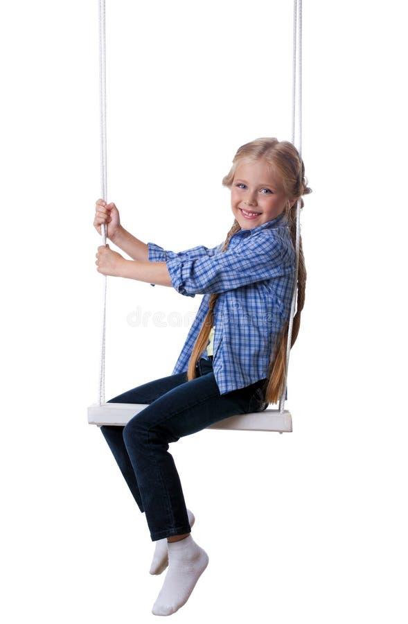 Lycklig blond flicka som sitter på swing arkivfoto