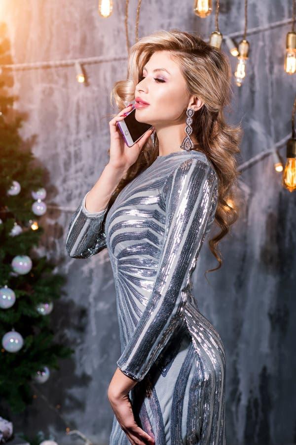 Lycklig blond flicka som stannar till telefonen Julstående av den härliga kvinnan arkivbild