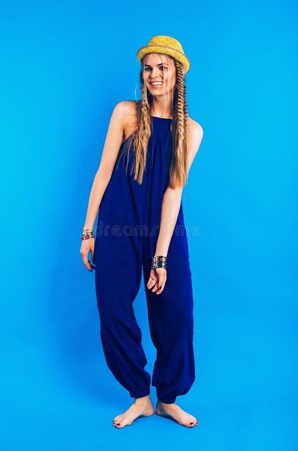 Lycklig blond kvinna i blå overall och gulinghatt royaltyfria foton