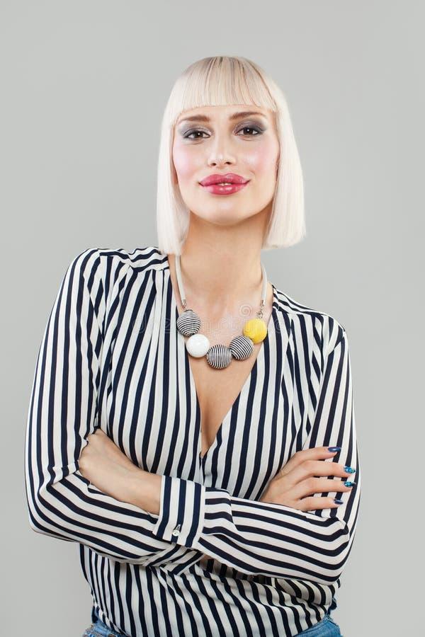 Lycklig blond kvinna med korsade armar på Gray Wall royaltyfri foto