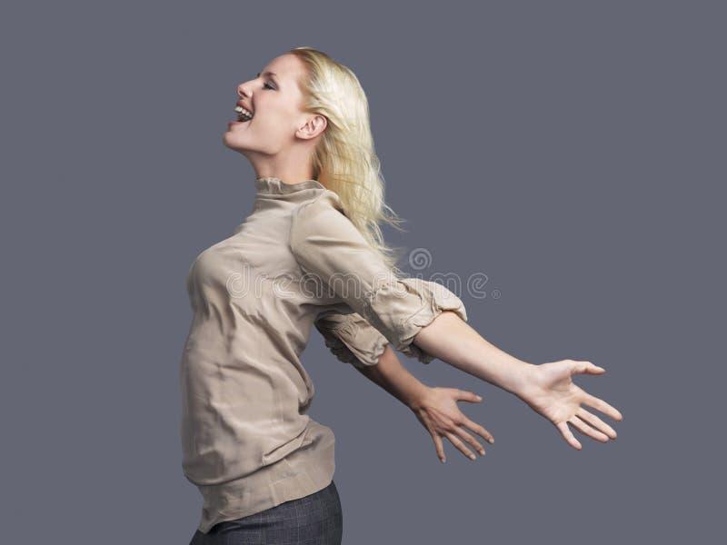 Lycklig blond kvinna med utsträckta armar royaltyfri foto