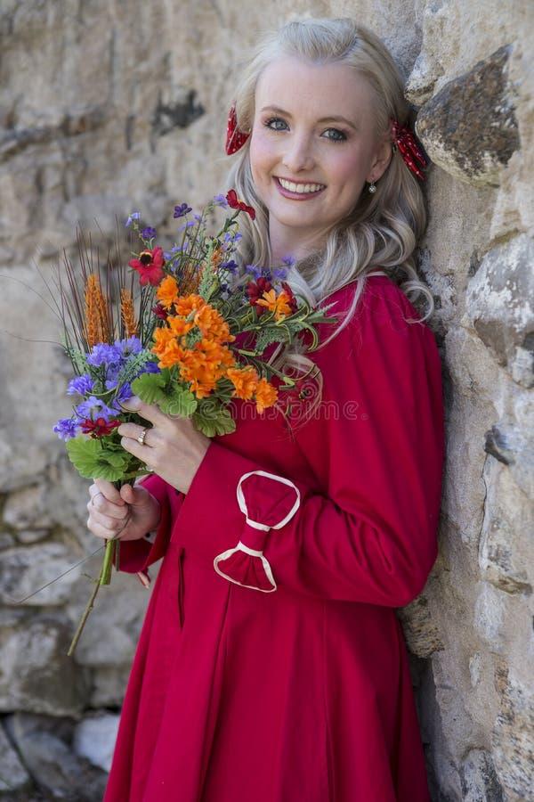 Lycklig blond kvinna som rymmer blommor arkivfoto