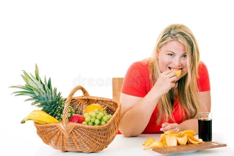 Lycklig blond kvinna som väljer att äta skräpmat arkivfoton