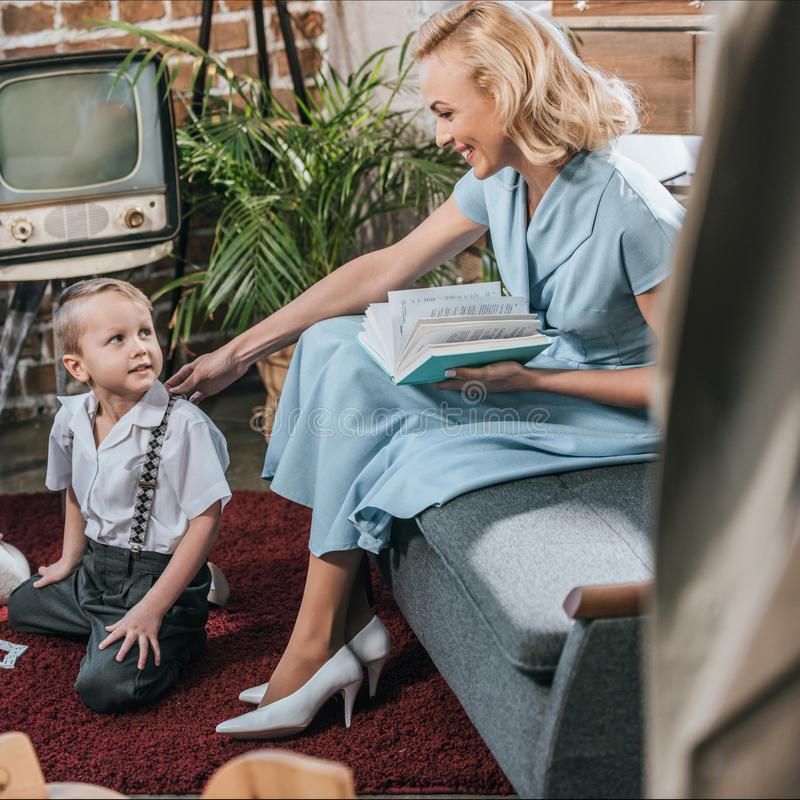 lycklig blond kvinnaläsebok och se den gulliga lilla sonen som hemma spelar på 50-tal för matta royaltyfri bild