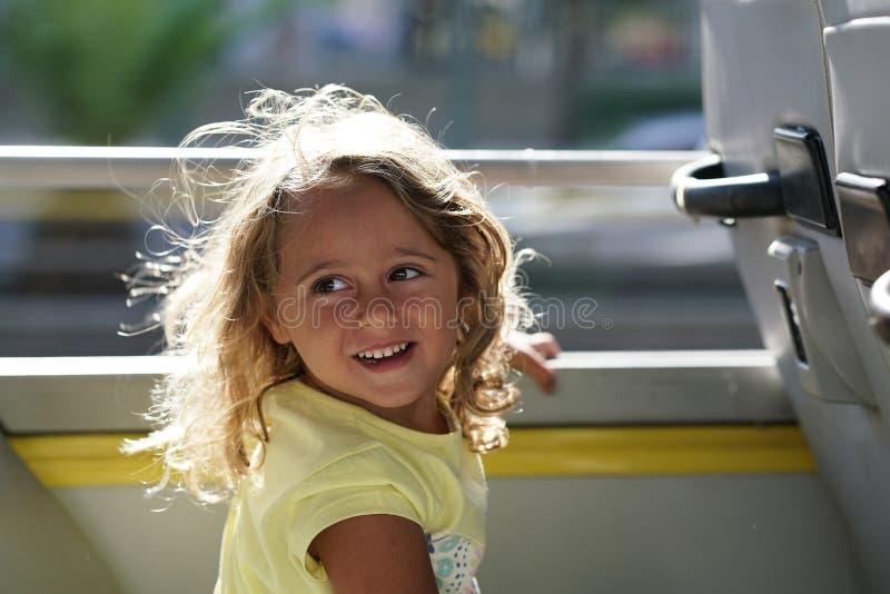 Lycklig blond liten flicka i den turist- bussen royaltyfri foto