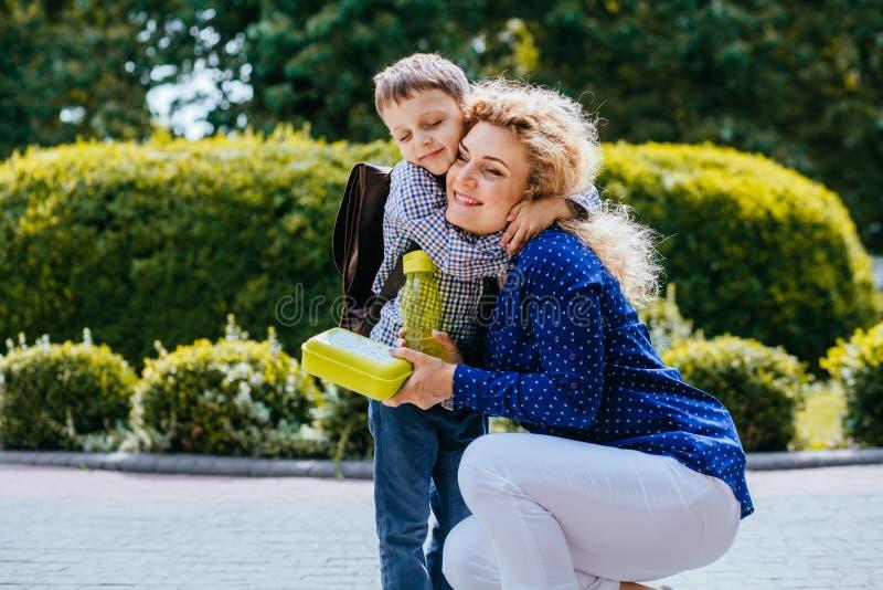 Lycklig blond lockig moder som kramar le den bärande skolväskan för son som ger honom en utomhus- skolalunchask Känslasinnesrörel royaltyfri bild