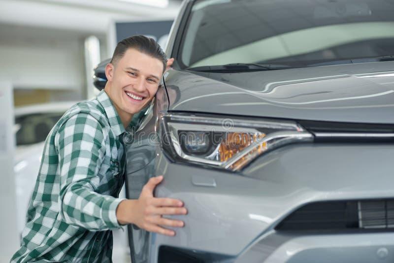 Lycklig blond man som ler, når att ha köpt hans första bil arkivfoton