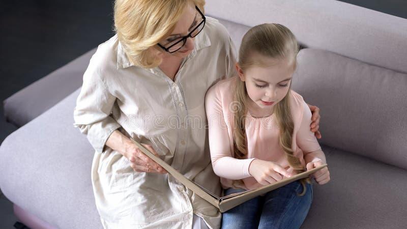 Lycklig blond sondotterläsebok med hennes att bry sig farmor, samhörighetskänsla royaltyfria foton