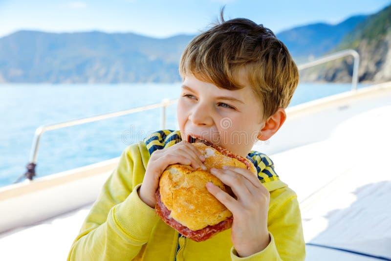 Lycklig blond ungepojke som tycker om segelb?ttur Familjsemestrar p? havet eller havet p? solig dag Sund h?rlig skola royaltyfria foton