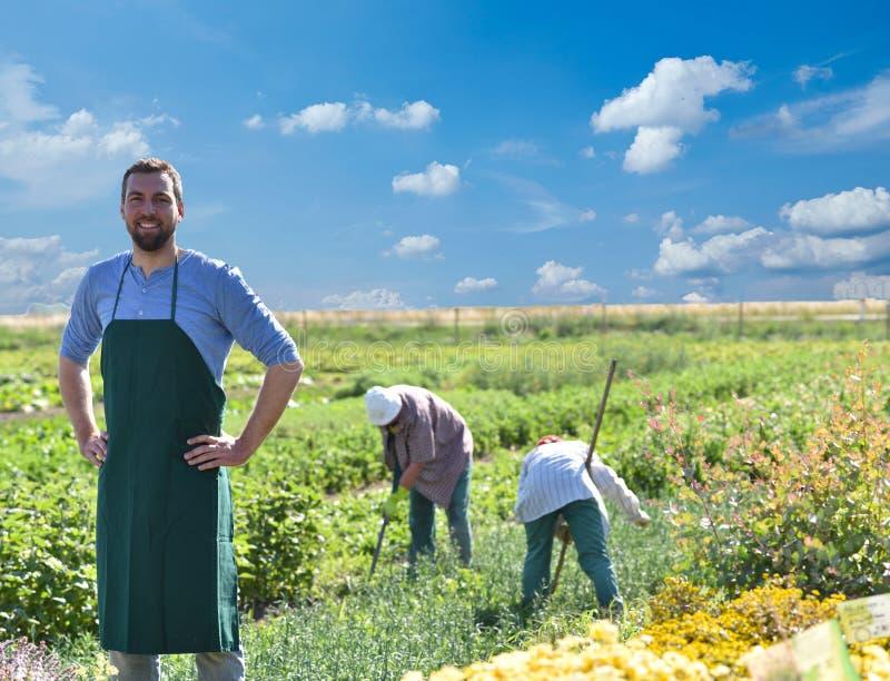 Lycklig bonde som växer och skördar grönsaker på lantgården royaltyfri fotografi