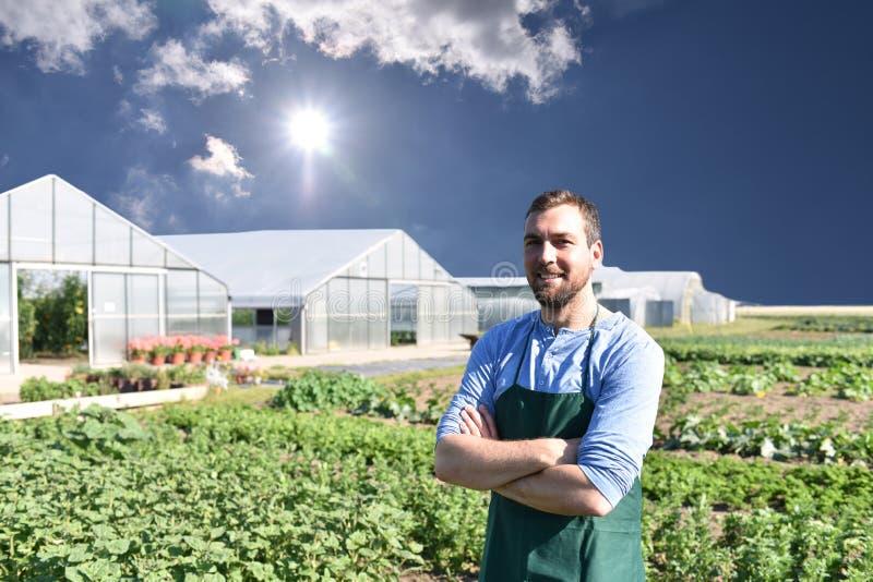 Lycklig bonde som växer och skördar grönsaker på lantgården royaltyfri foto