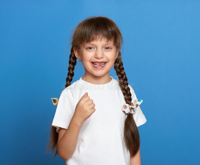 Lycklig borttappad tandflickastående, studiofors på blå bakgrund royaltyfri foto