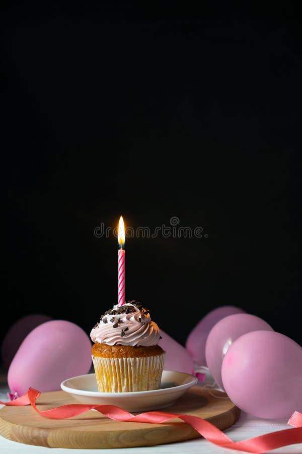 Lycklig brithday muffin med en stearinljus på en svart bakgrund royaltyfri foto
