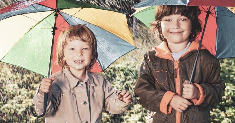 Lycklig broder med paraplyet utomhus royaltyfri bild