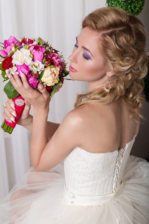 Lycklig brud för härlig försiktig ung flicka, i ett vitt klänningsammanträde på en stol och att lukta en brud- bukett med en trev royaltyfri foto