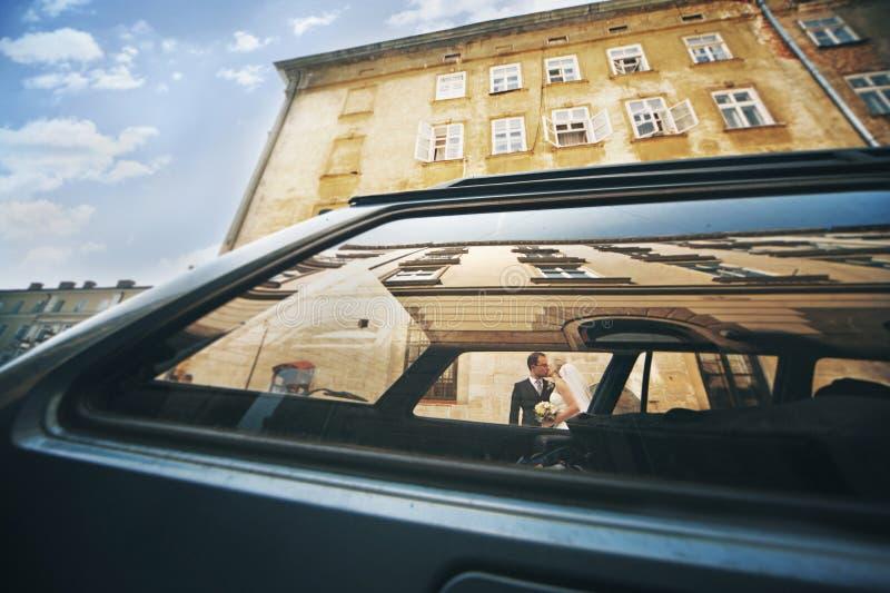 Lycklig brud i brudgummen som framme kysser av byggnad, skott igenom arkivbilder
