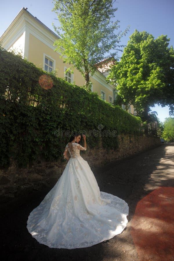 Lycklig brud, innan att gifta sig Härliga bröllopsklänningar i boutique Underbar brud- kappa kvinnan förbereder sig för att gifta royaltyfria foton