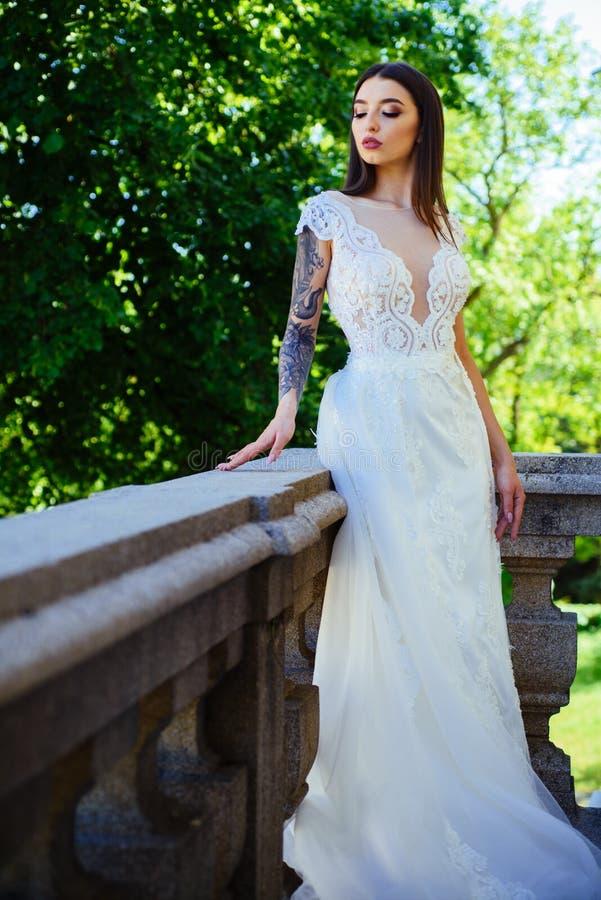 Lycklig brud, innan att gifta sig Härliga bröllopsklänningar i boutique Underbar brud- kappa kvinnan förbereder sig för att gifta arkivfoto