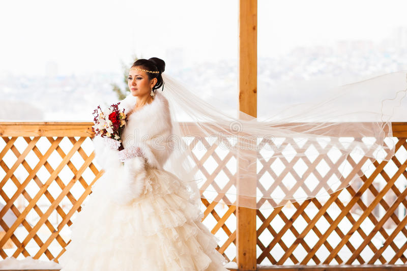 Lycklig brud med den väntande på brudgummen för bukett i vinterbröllopdag royaltyfri fotografi
