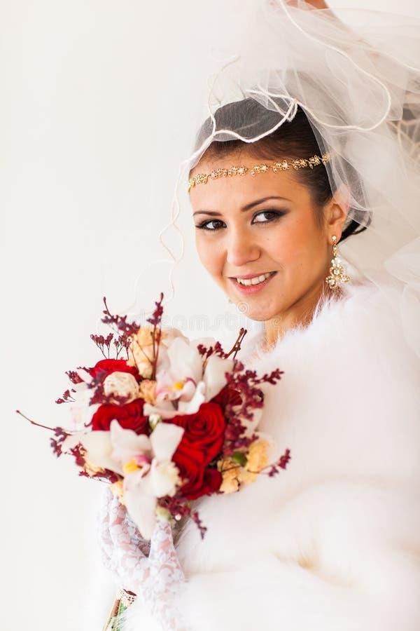 Lycklig brud med den väntande på brudgummen för bukett- och diamantsmycken i vinterbröllopdag royaltyfri bild