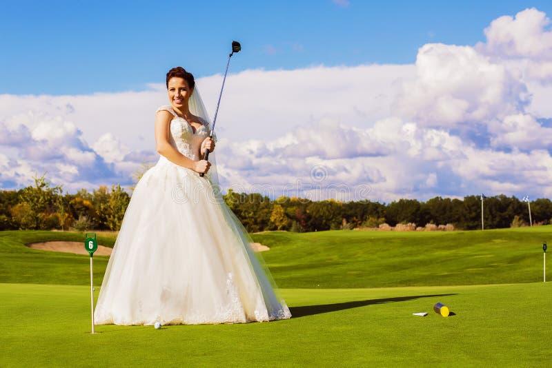 Lycklig brud med trä på golffält arkivbild
