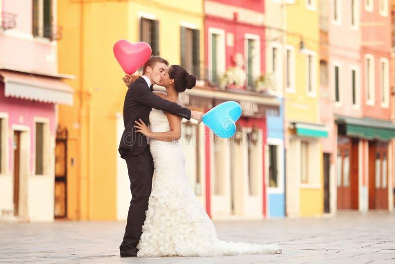 Lycklig brud och brudgum i Venedig med ballonger royaltyfri foto