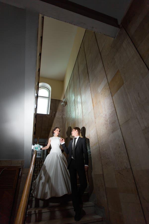 Lycklig brud och brudgum på den mörka trappan arkivfoto