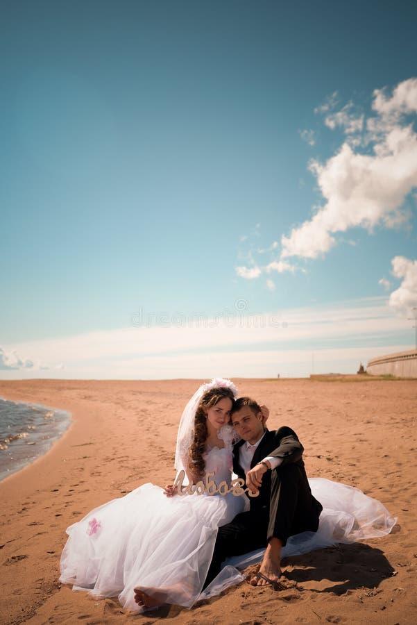 Lycklig brud och brudgum på deras bröllop nära havet royaltyfri bild