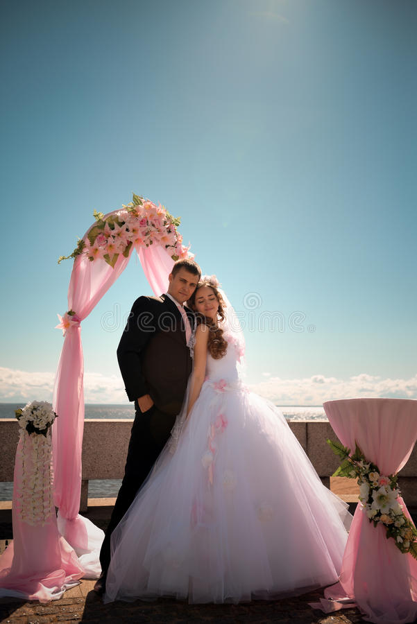 Lycklig brud och brudgum på deras bröllop nära havet arkivbilder